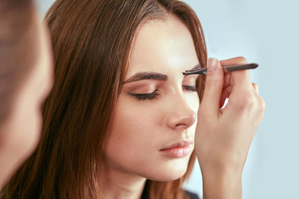 Beautician shaping woman's eyebrows