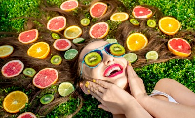 Woman lying down with various fruits in hair