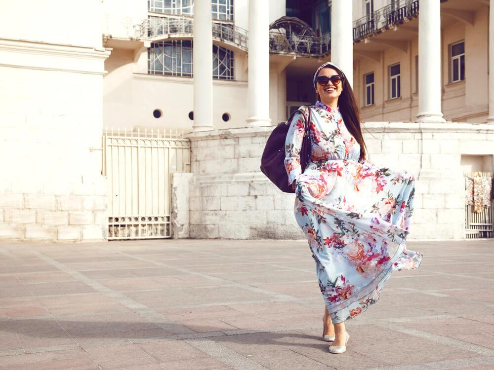 woman wearing a maxi dress near historical building