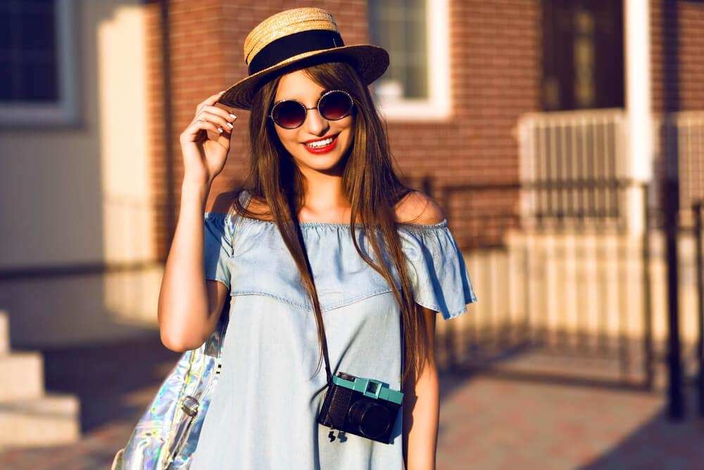 woman with camera and sunhat smiling in the sun