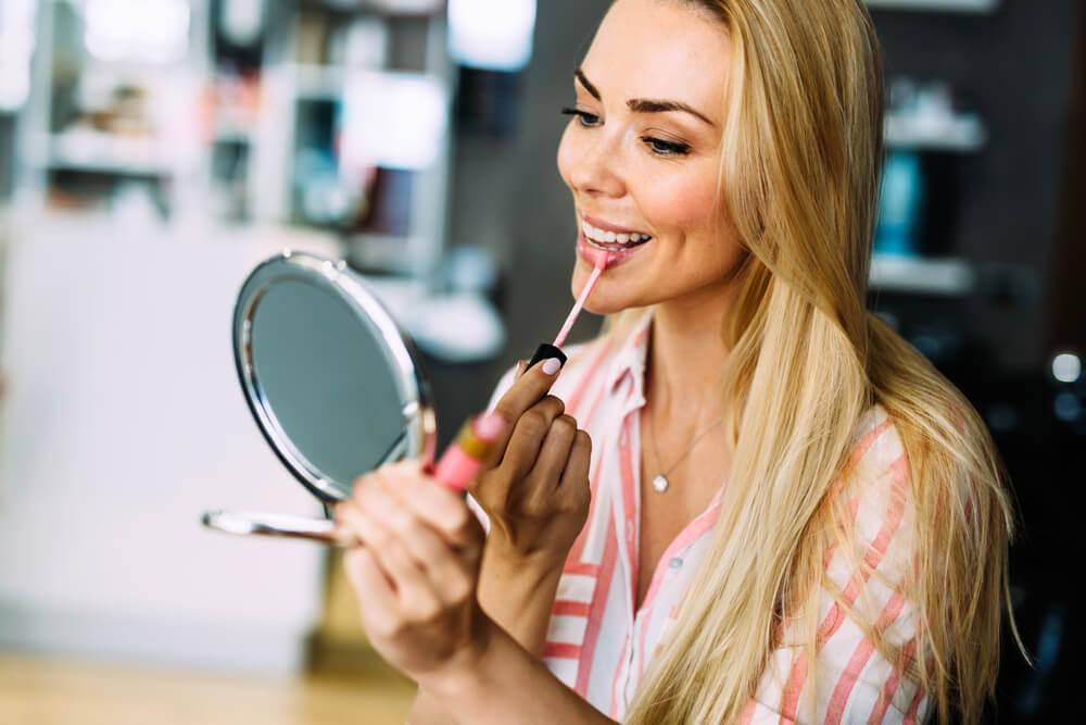 woman applying makeup at home