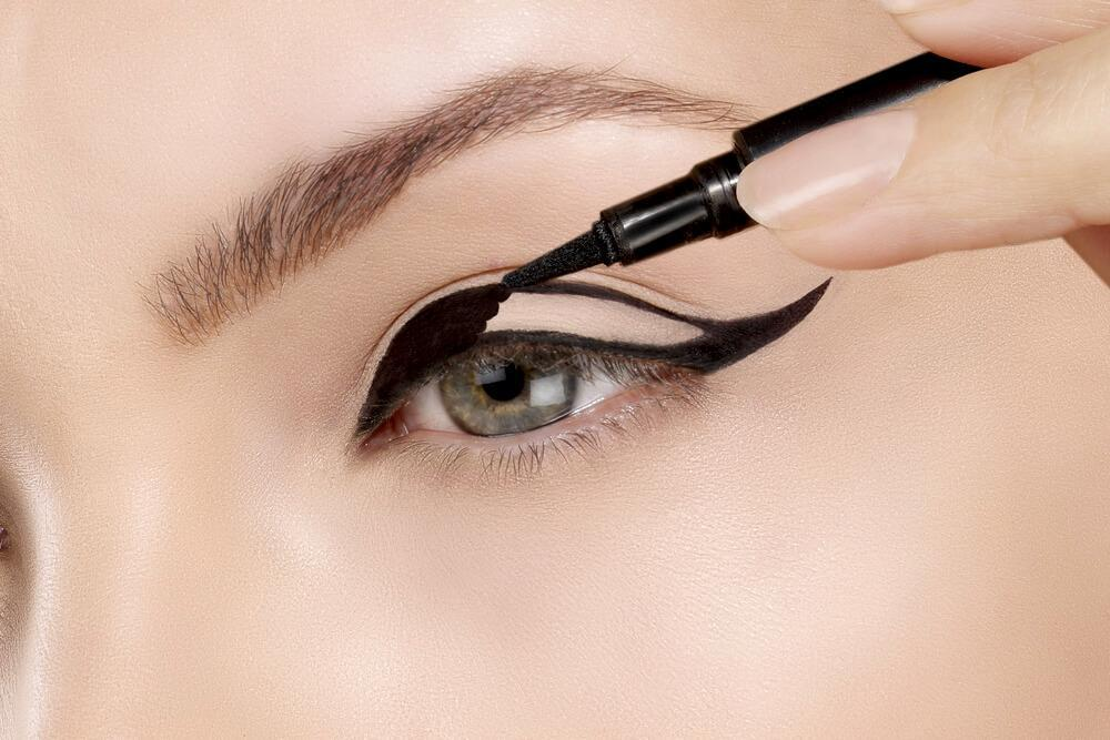 applying dark eyeliner to achieve dramatic look