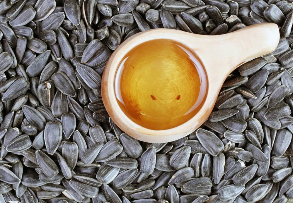 Spoonful of oil surrounded by sunflower seeds
