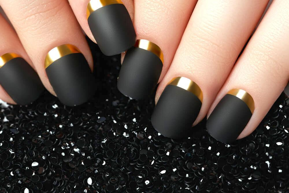 Matte black and gold nail art design
