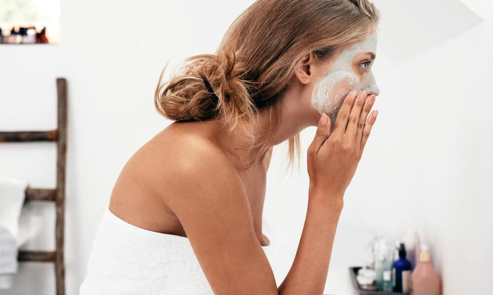 Woman applying face mask to skin in front of mirror