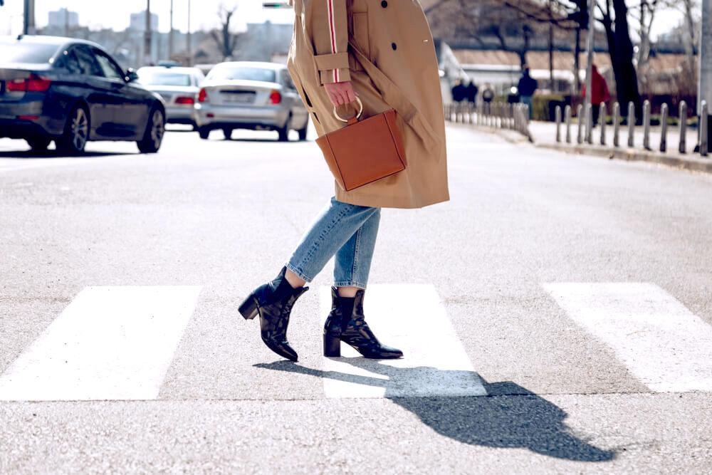 Unknown woman in trench coat, denim jeans and ankle boots