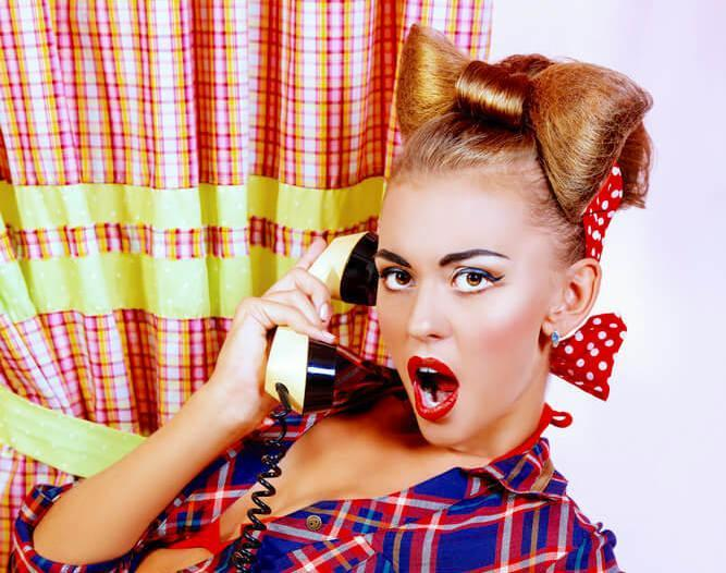 Surprised pinup girl with a hair bow bun, using an old telephone
