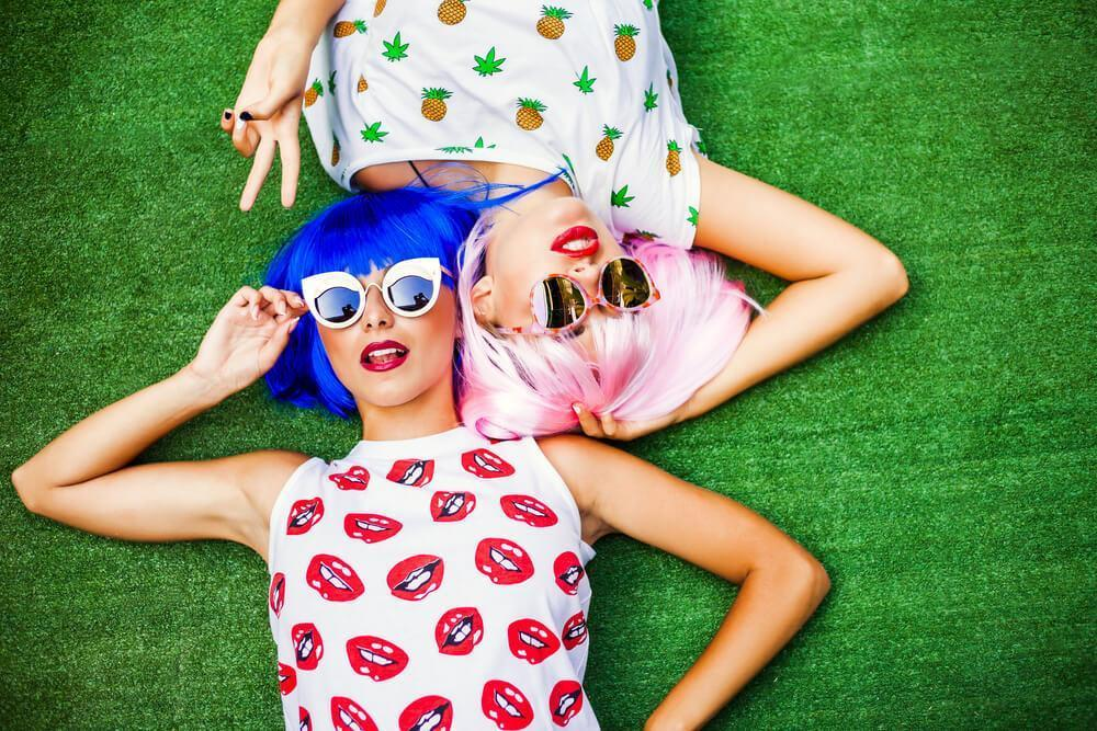 Two young woman with colourful hair wigs and fashionable sunglasses lying on the grass