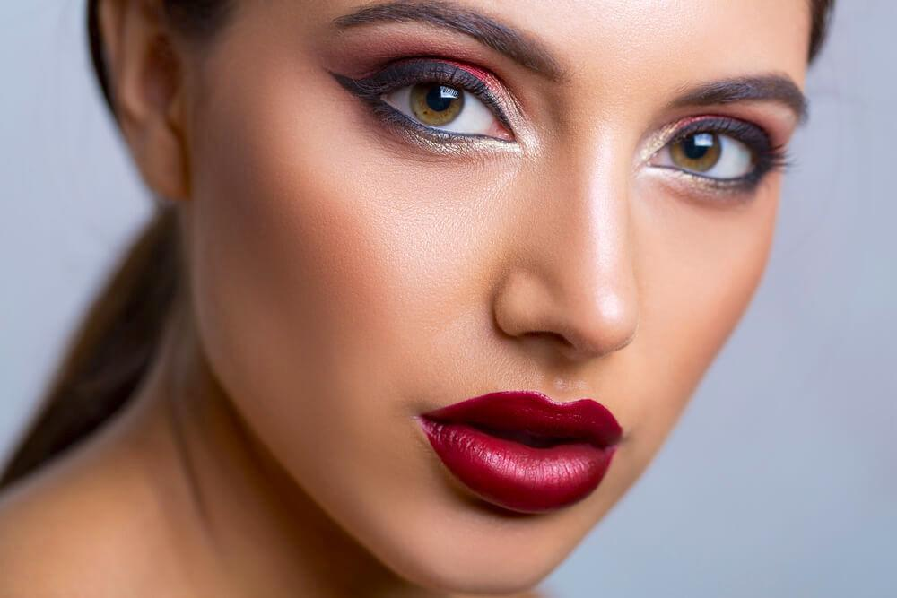 Beautiful woman with deep berry lipstick and bright eye makeup
