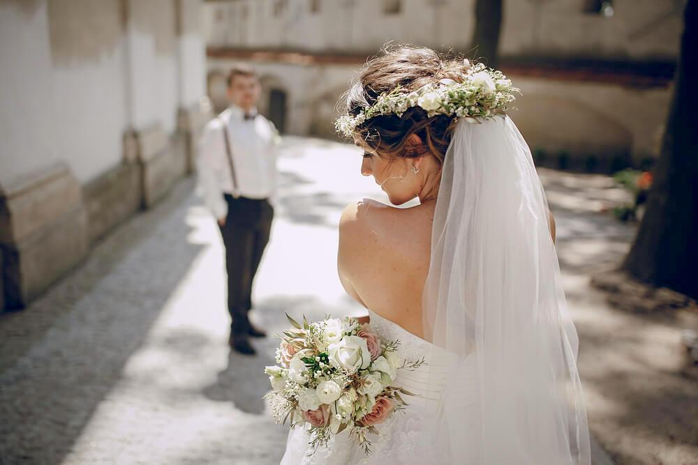 Young bride in veil and flower garland, groom standing in the distance