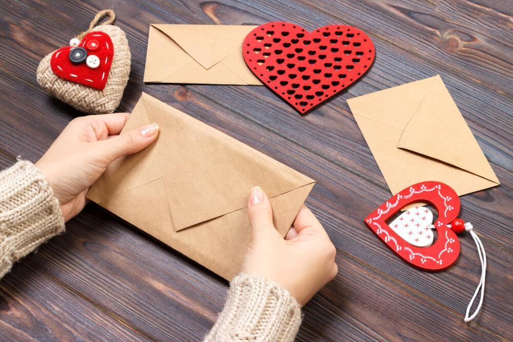 Preparing Valentine's Day greeting cards in envelope
