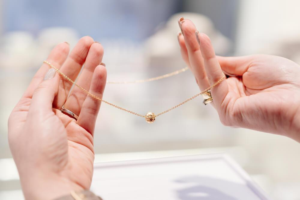 Female hands holding up a delicate necklace