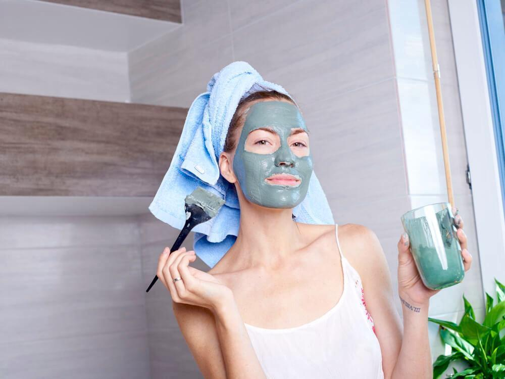 Woman applying green clay face mask in bathroom