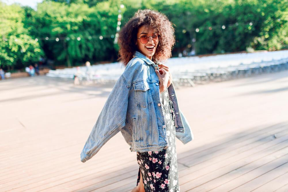 Happy smiling woman with denim jacket on the beach
