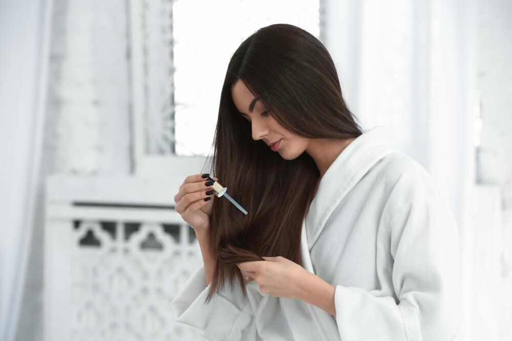 Woman applying hair serum to long straight hair