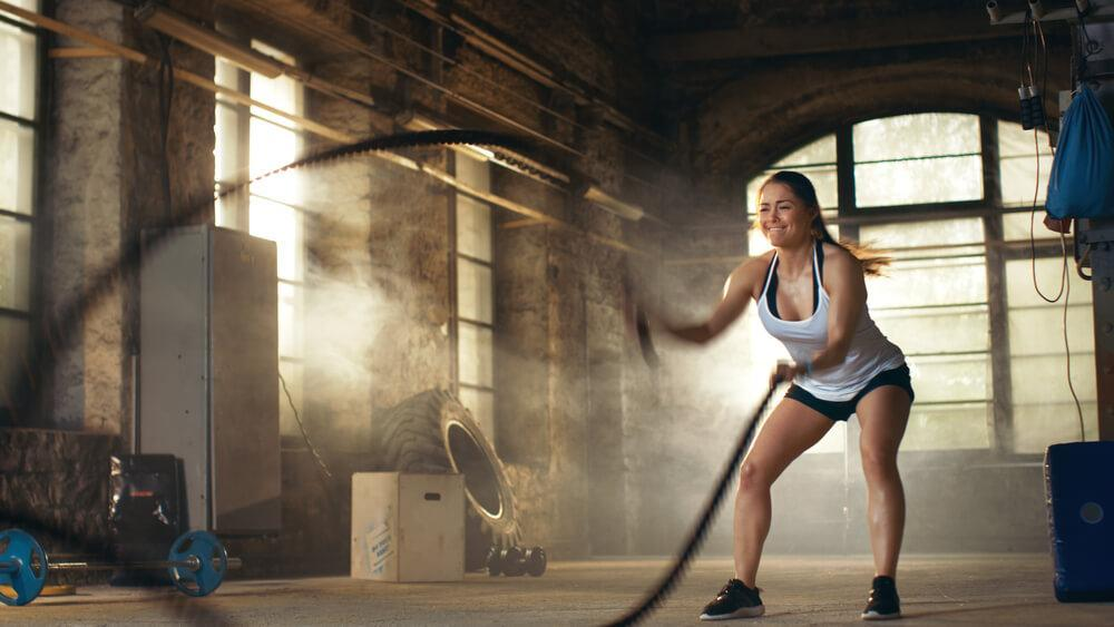 Woman working out in the gym using thick rope