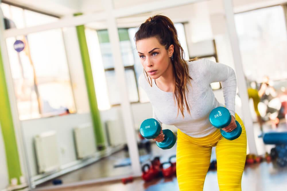 Woman working out with dumbbells at the gym