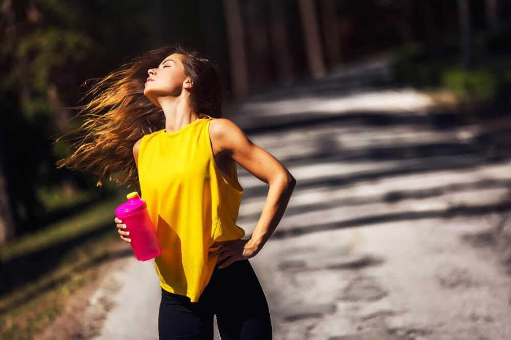 Athletic woman flipping her hair while holding water bottle