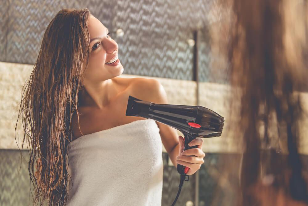 Woman in towel blow drying hair