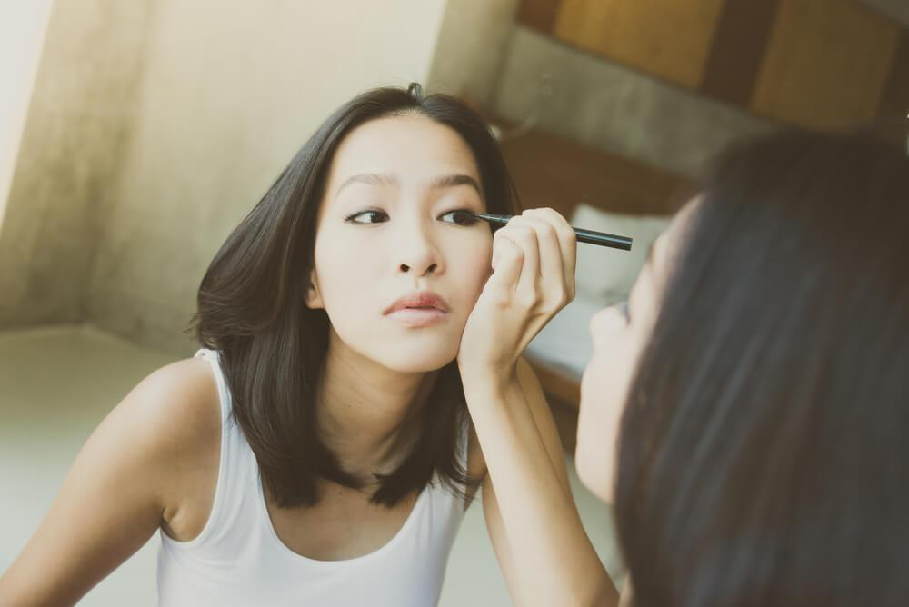 Woman applying eyeliner in front of mirror