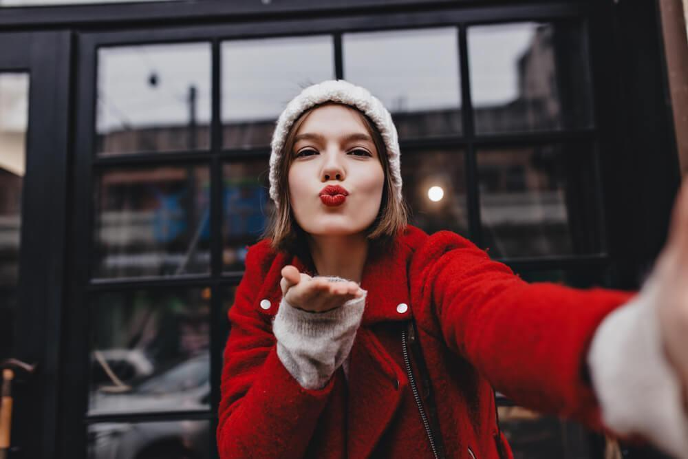 Woman with red lipstick blowing a kiss at camera