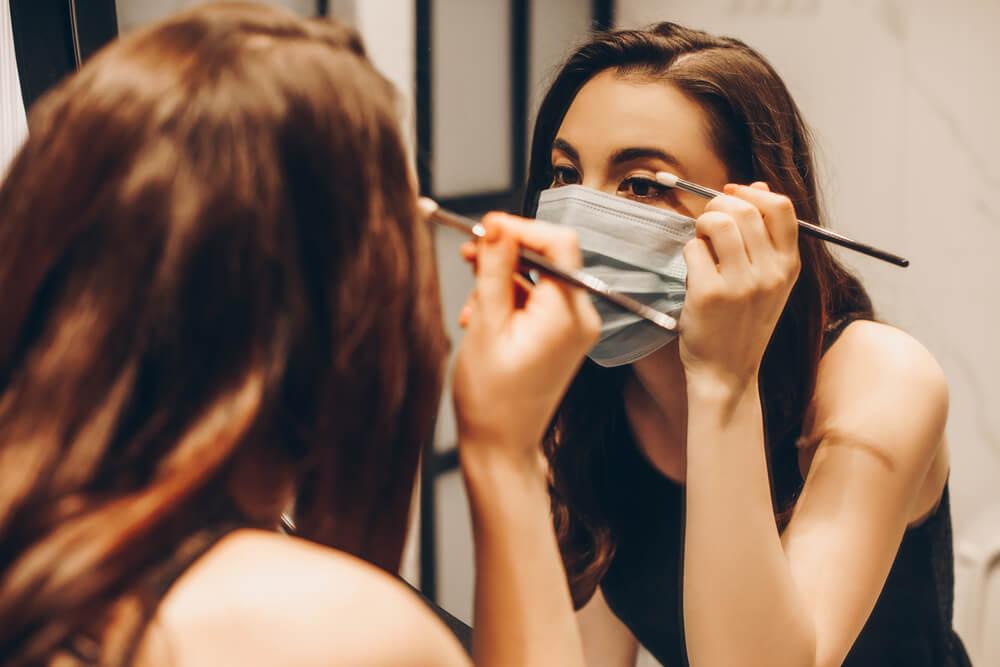 Woman applying eye makeup in mirror while wearing face mask