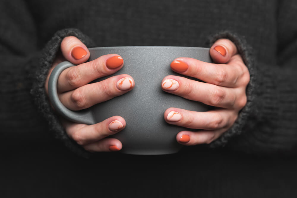 Hands holding mug with manicured nails