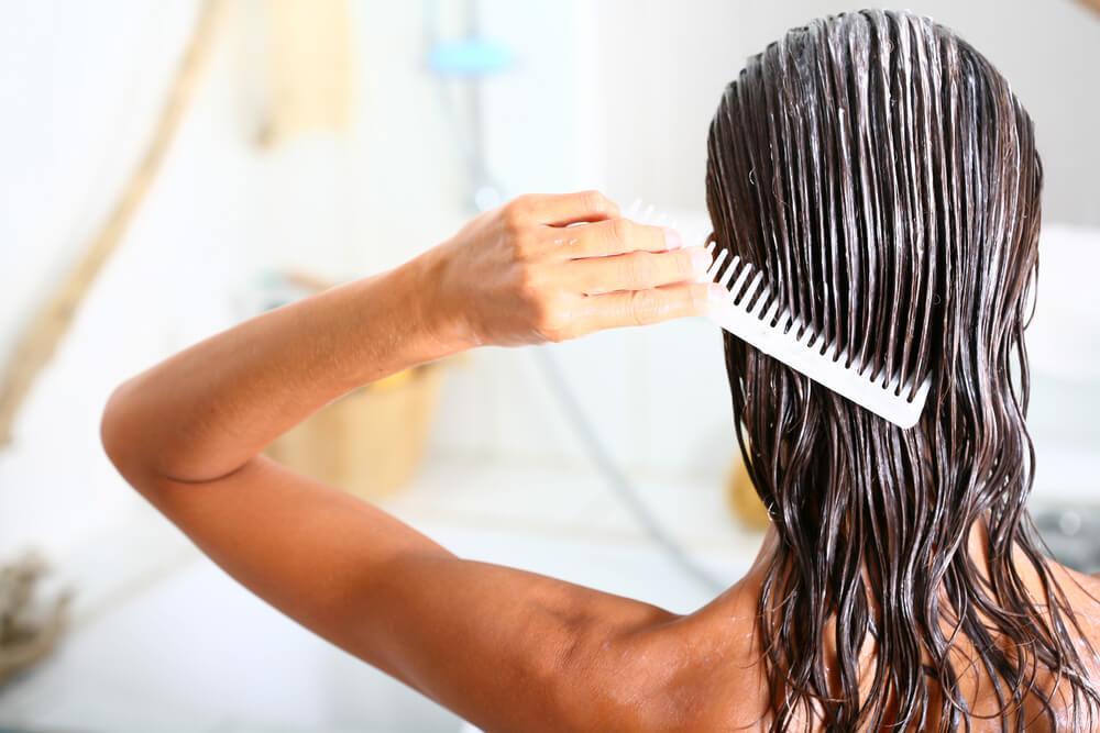 Woman combing conditioner through hair