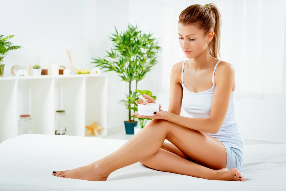 woman using body lotion