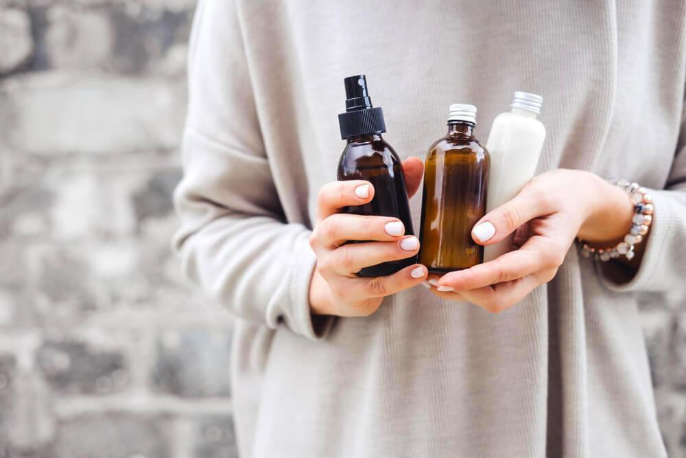 Unknown woman holding up essential oils in her hands
