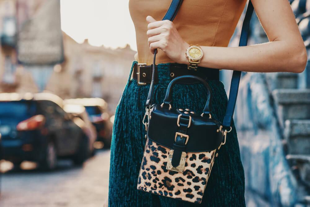 Woman with blue skirt and leopard print bag