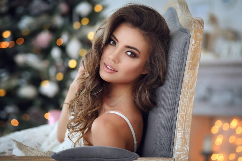 Woman wearing makeup sitting by Christmas tree