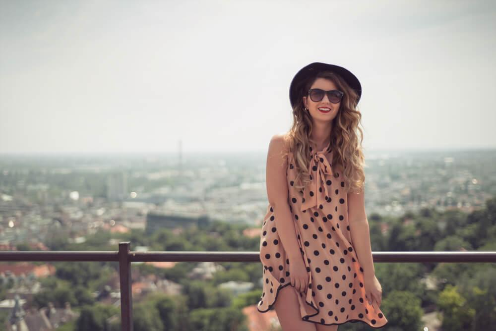 Woman in polka dot dress standing at balcony outside