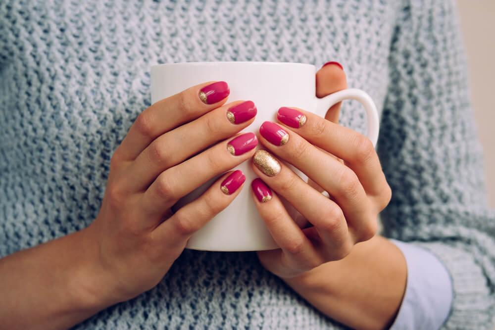 Woman with manicure holding mug