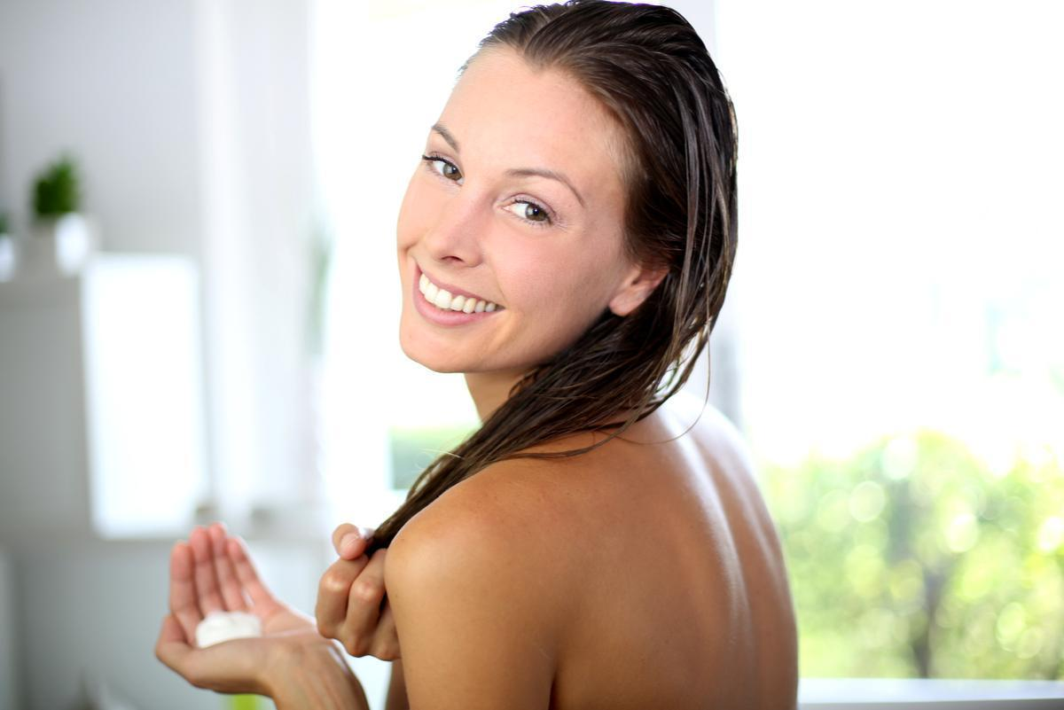 Woman in bathroom about to use a hair scrub