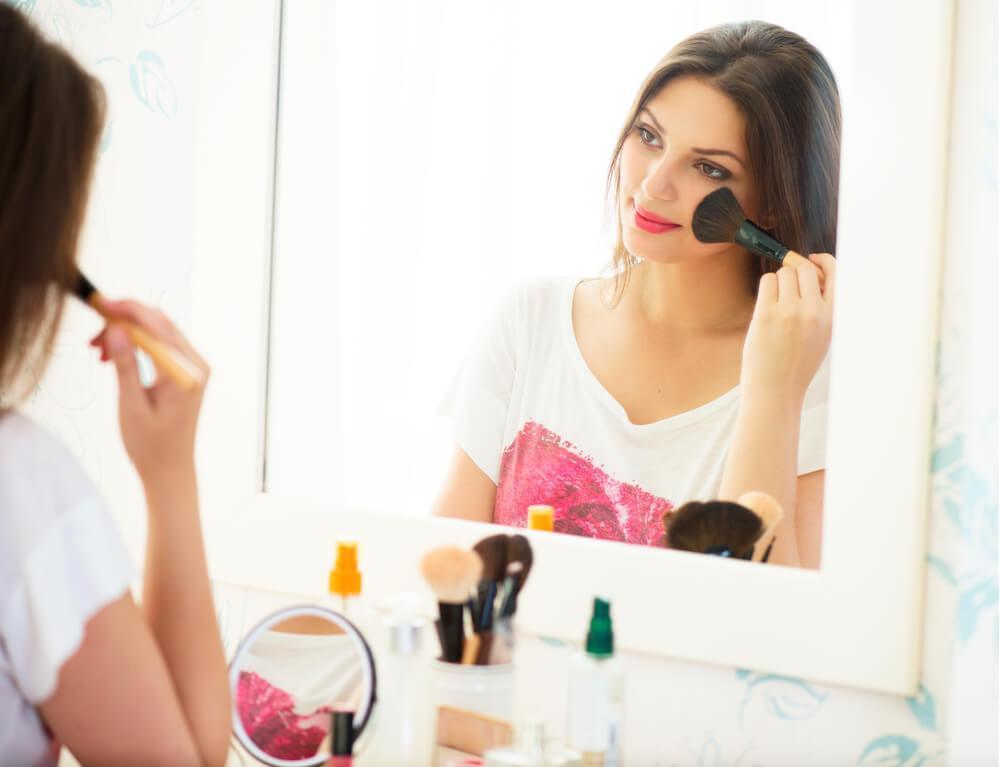 Woman applying makeup in front of mirror